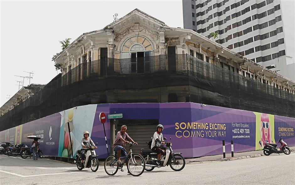 Under wraps: Road users passing by a row of heritage buildings covered up with purple hoarding at the Jalan Gurdwara-Lebuh Noordin junction. u2014 ZHAFARAN NASIB/The Star