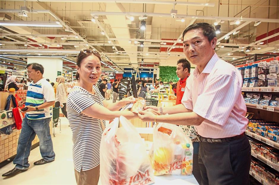 The first customer of Jaya Grocer at Sunway Citrine Hub receiving her purchased items from store manager Liew Choon Chee.
