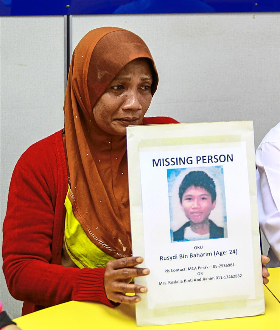 Hospital housekeeper Roslaila Abd Rahim, 48, holding the photograph of her missing son Rusydi Baharim, 24, during a press conference held by Perak MCA Public Service and Complaint Bureau chief Jimmy Loh on Thursday (sept 18).