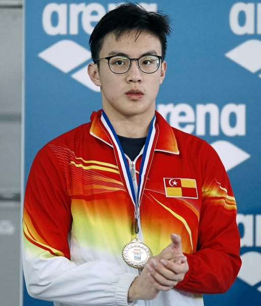 Well done!: Ng Jing Fu smashed the 100m breaststroke national record in the Malaysian Open at the National Aquatics Centre in Bukit Jalil yesterday. Inset: Jing Fu posing with the gold medal. — S.S. KANESAN/The Star