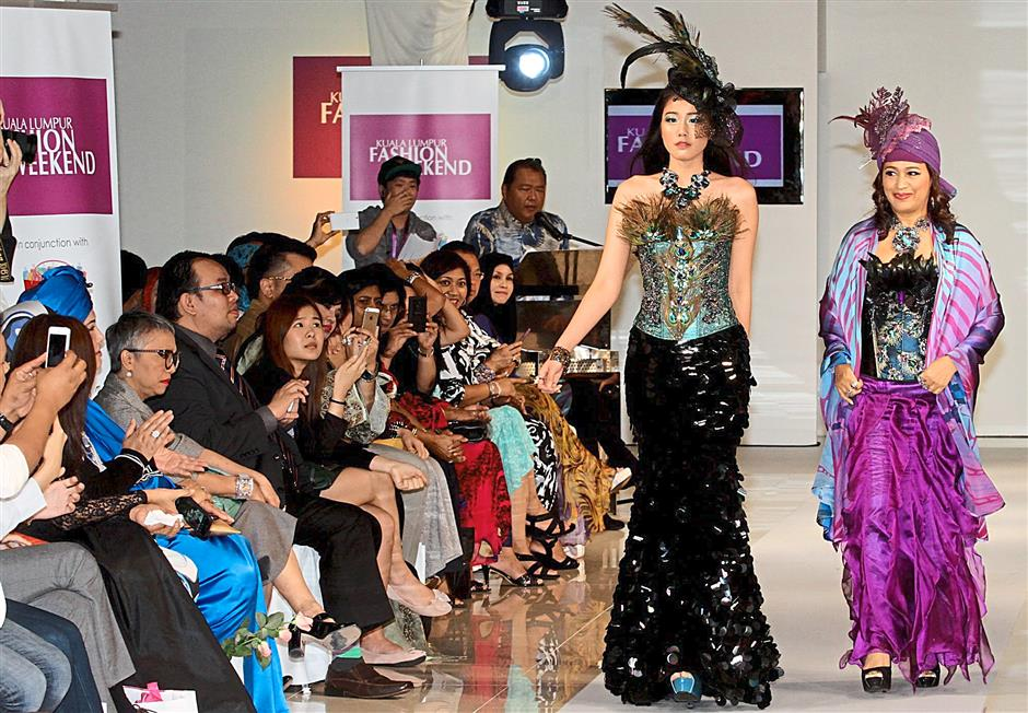 Miss Malaysia World 2014 Dewi Liana Seriestha (left) doing the catwalk with accessory label designer Axxezz Gina Frias.