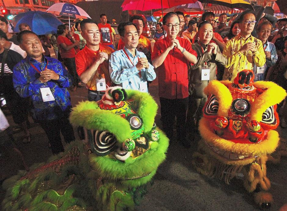 Dr Mah (centre, in red) greeting the guests at the opening of the event flanked by the lion dance group.