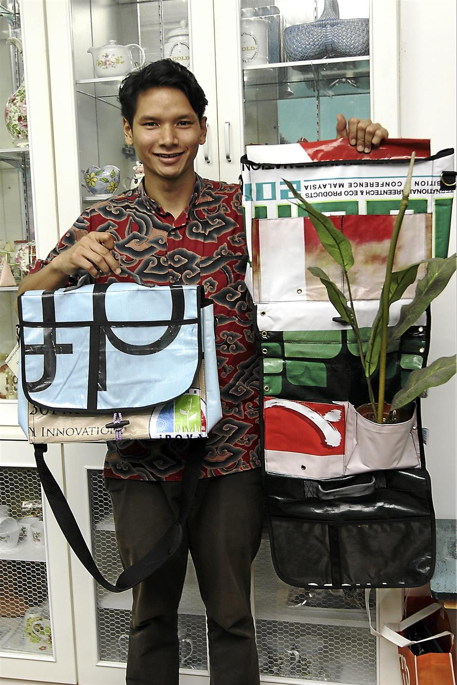 Volunteer Azam Hisham with items made by the kids at the association, banners upcycled into bags.
