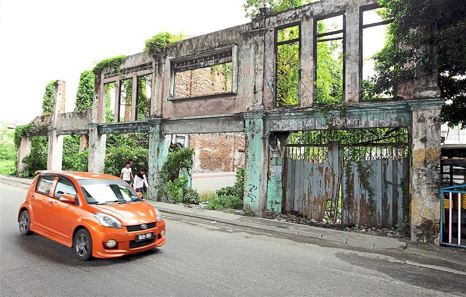 A car passes by derelict colonial buildings along Jalan Kem in Port Klang.