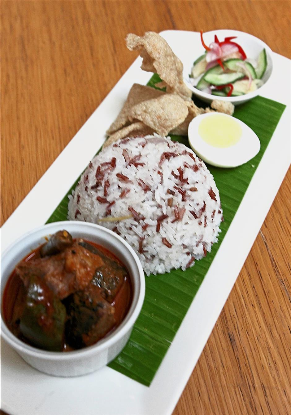 Nasi dagang served with chicken curry, hard boiled egg and fish crackers.