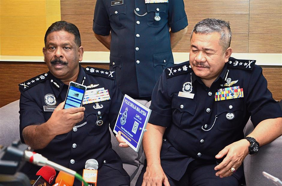 Comm Thaiveegan (left) showing the device used to scan the QR code of the CoPS box. Looking on is Deputy Comm Roslee.