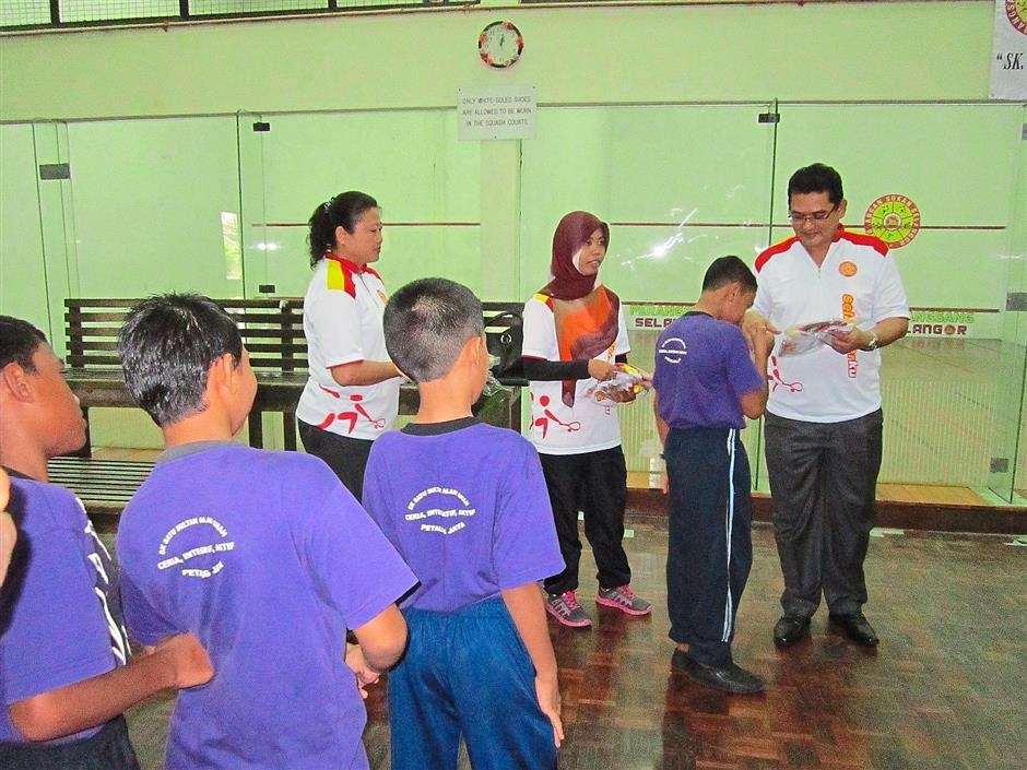 In appreciation: Mohd Fauzi (standing right) presenting the children with T-shirts during the launch.