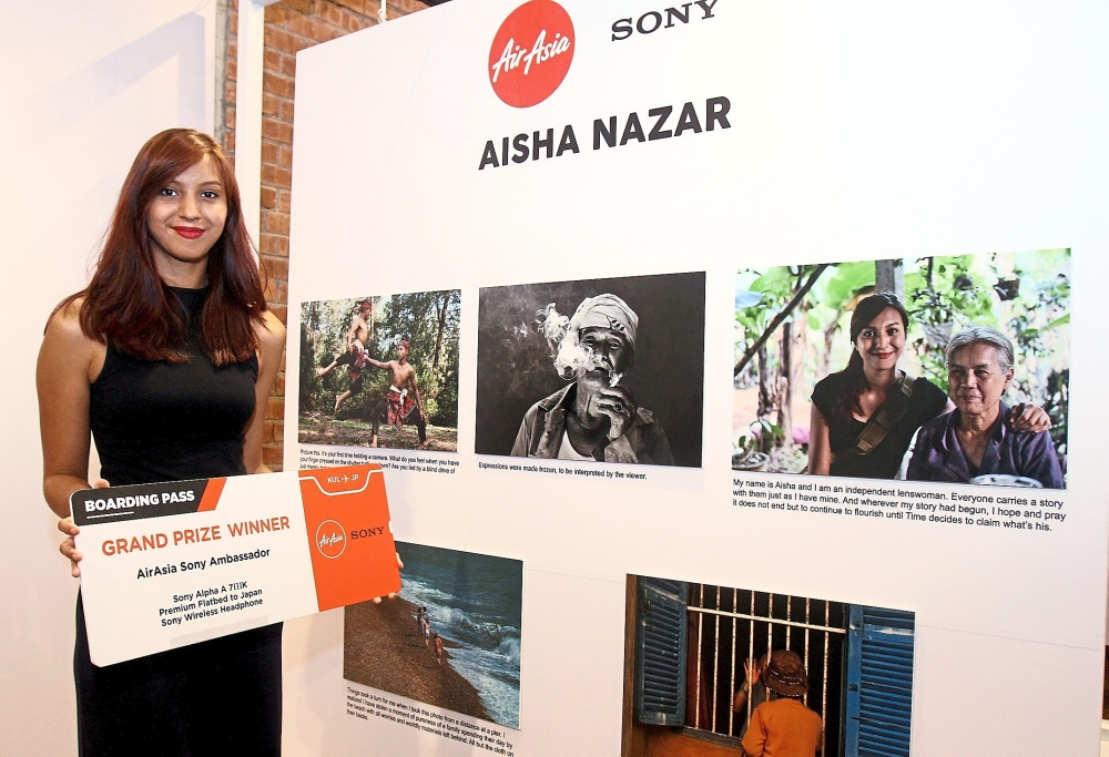 Aisha with some of the photographs at the winner's announcement event.