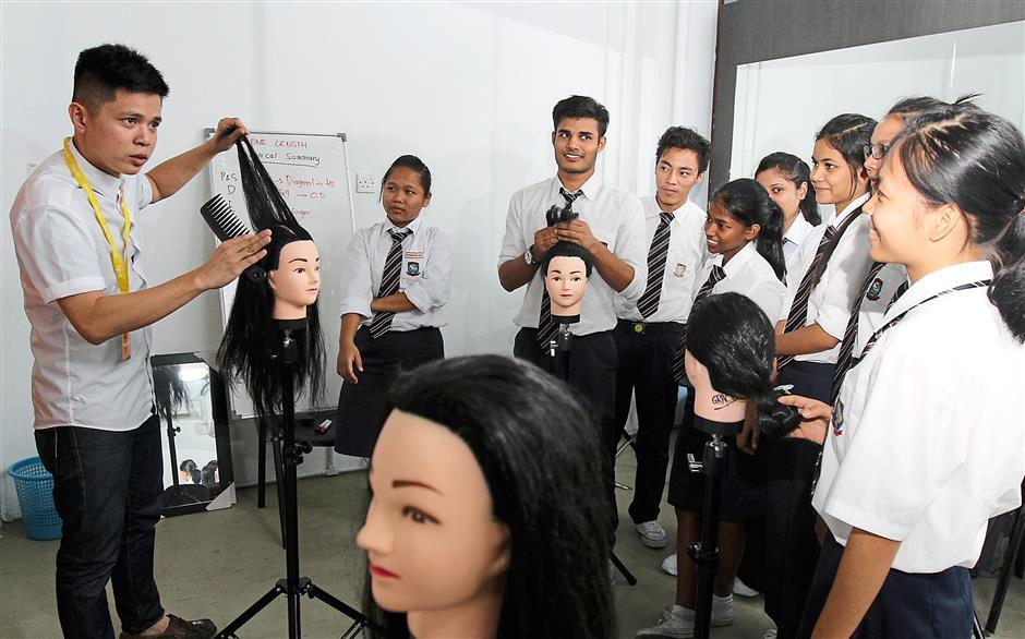 Low (left) travels to the centre twice every week to teach the refugee the ways of hairdressing.