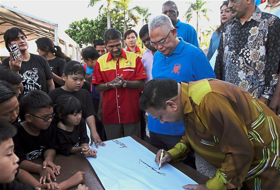 (From right) Vigneswaran writing his wishes on a giant scroll while Noh Omar and Karan look on during the event.