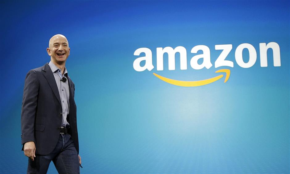 FILE - In this June 16, 2014, file photo, Amazon CEO Jeff Bezos walks onstage for the launch of the new Amazon Fire Phone, in Seattle. In a milestone announced Tuesday, March 6, 2018, Bezos has become the first person to amass a fortune surpassing $100 billion in Forbes magazineu2019s annual ranking of the worldu2019s moguls. (AP Photo/Ted S. Warren, File)