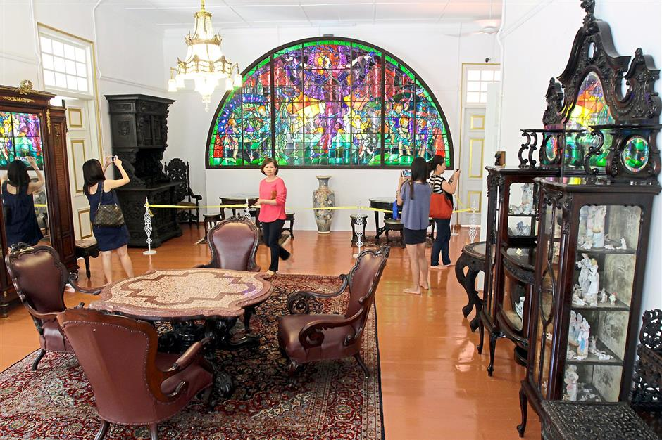 Historical charm: Visitors admiring East Indian-styled furniture at the Colonial Penang Museum. Seen in the background is a half-moon stained glass panel made by William Morris (1834 -1896), founder of the Arts and Crafts movement in Britain.