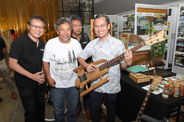 Fahmi (right) trying out a guitar made of bamboo from the Bamboo Jungle Adventures booth while (from left) Dr Tan, Design Principles director Rahim Ismail and KLAF 2019 team leader Amzar Ahmad look on.