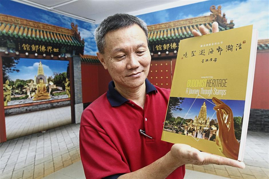 Hor showing the book on Leong's stamps collection entitled 'Buddhist Heritage: A Journey Through Stamps' which includes photos and explanation of stamps featured at the Buddhist stamps gallery in Yayasan Belia Buddhist Malaysia in Penang.