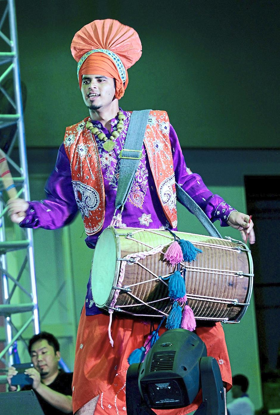 Infectious beats: A drummer representing Malaysia in the Bhangra dance troupe giving an energetic performance.