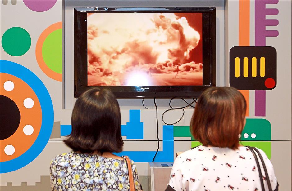 Visitors viewing an interactive display of a nuclear explosion at the Peace Exhibition.
