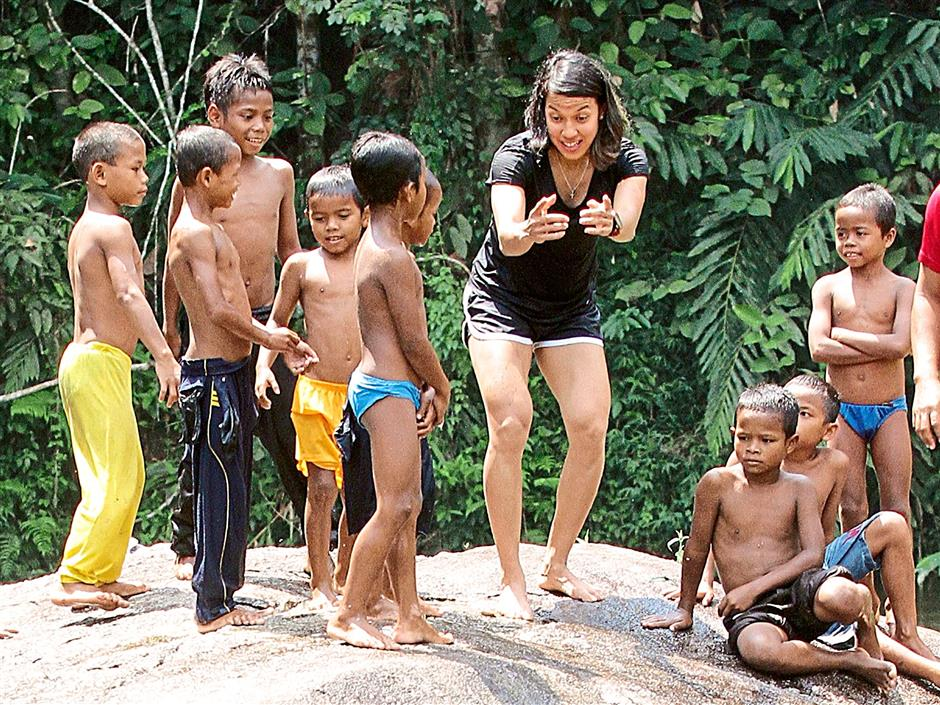 Nicol taking time off squash to interact with orang asli children earlier this year as UNDP Goodwill Ambassador.