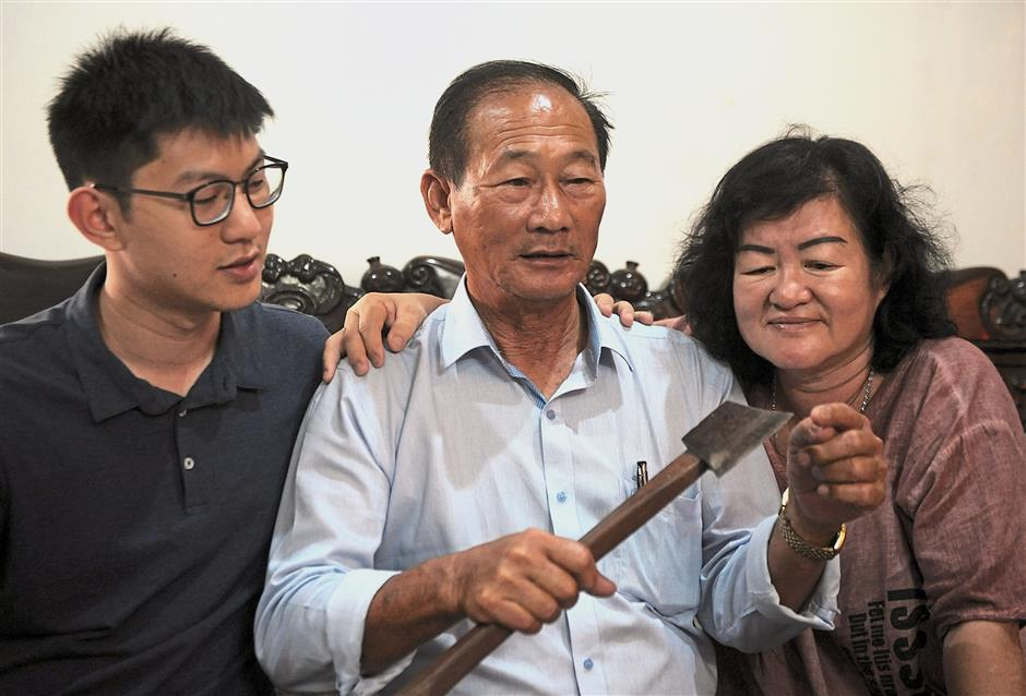 This is how I did it: Oon showing his wife, Tan Mooi Chen, 60, and son Chin Liang, 24, the axe he used to save the family. — ASRI ABDUL GHANI / The Star