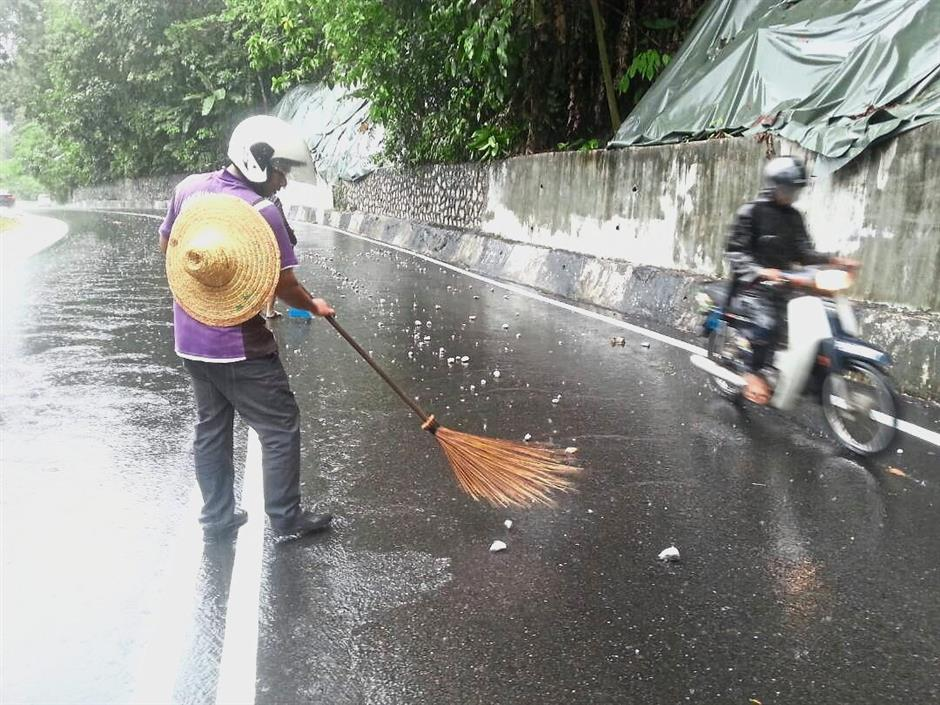 A Myanmar worker sweeping away small rocks along Jalan Paya Terubong.