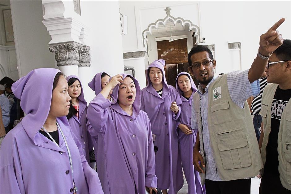 Tourists (in purple) admiring the architecture of Masjid Kapitan Keling.