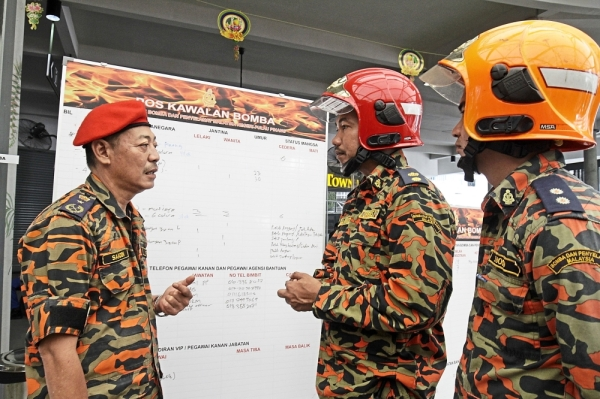 Saadon (left) briefing his men on the rescue mission. (Right pic) Two 'victims' being prepared to be evacuated during the simulation exercise.