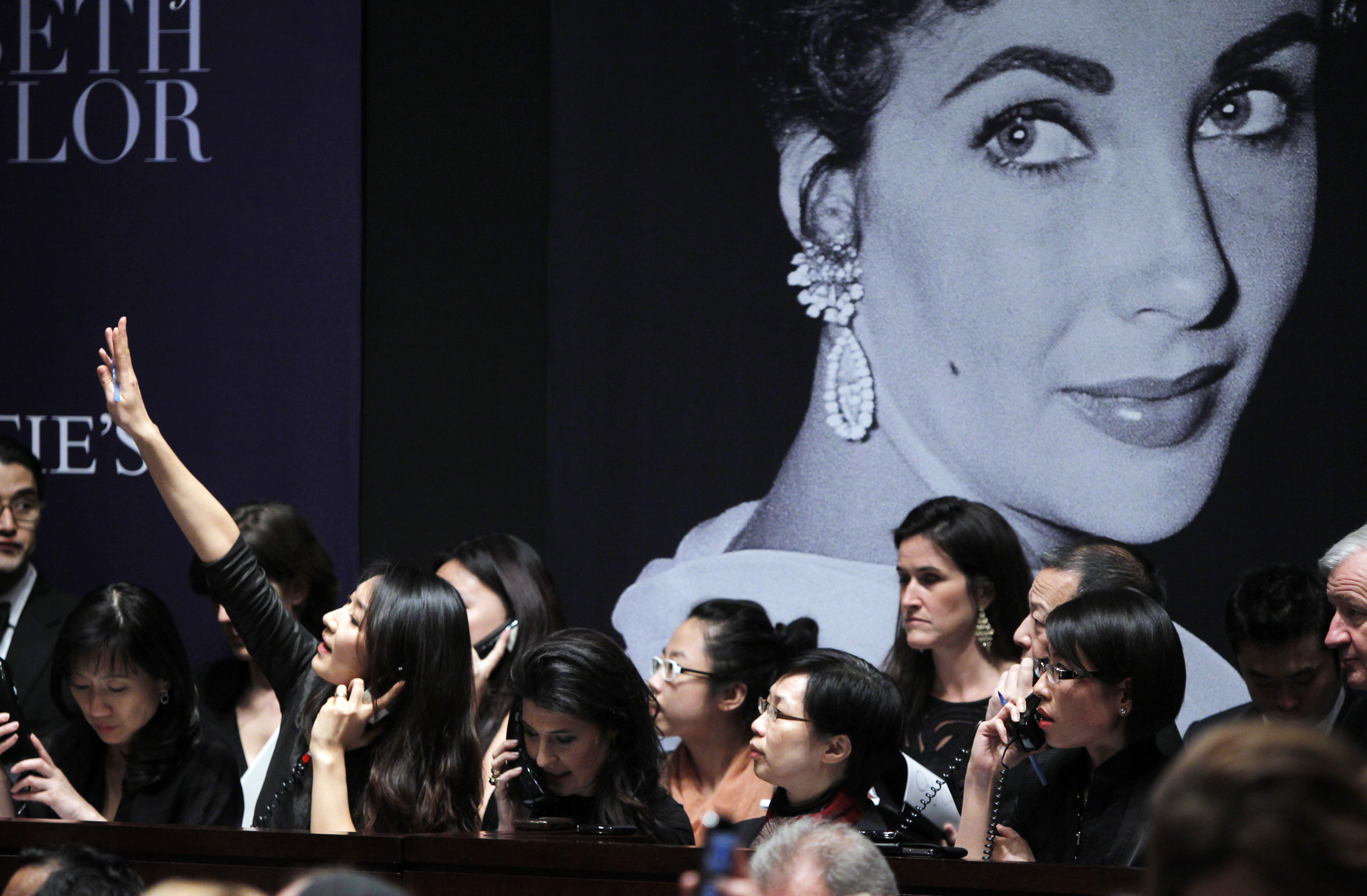 FILE PHOTO: A phone bidder signals her bid near an image of Elizabeth Taylor during an auction of the late actress' jewellery, clothing, art and memorabilia at Christie's Auction house in New York December 13, 2011. REUTERS/Carlo Allegri