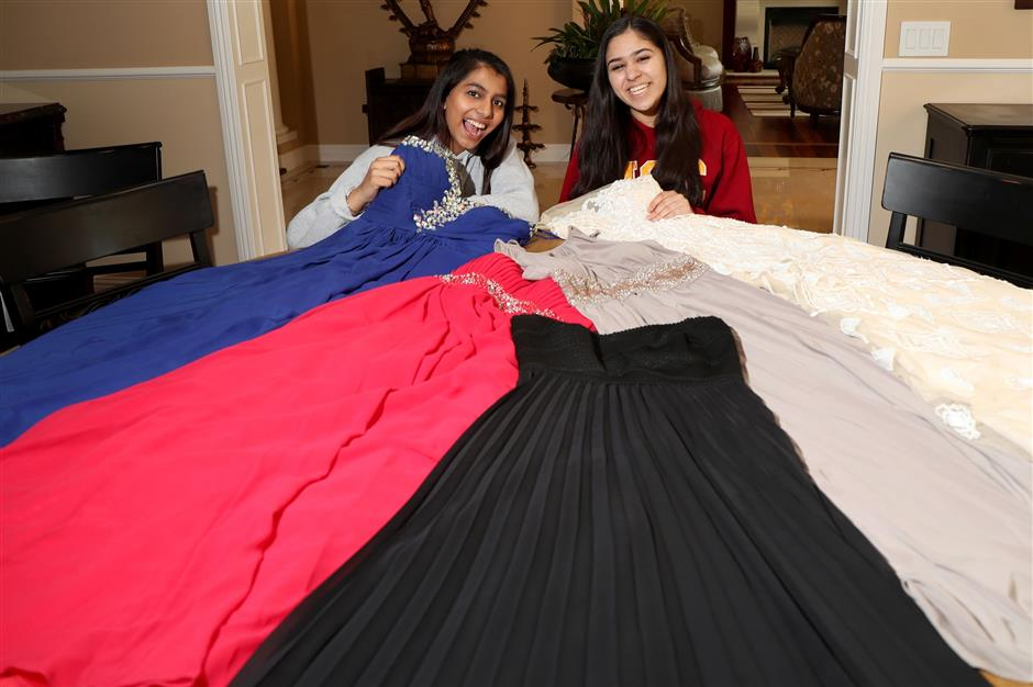 Nishka Ayyar, 16, left, and Riya Gupta, 17, of Saratoga, pose with prom dresses at Ayyar's home in Saratoga, Calif., on Wednesday, April 18, 2018. The junior high school students built the PromElle app designed for renting prom dresses to and from their users. (Ray Chavez/Bay Area News Group/TNS)