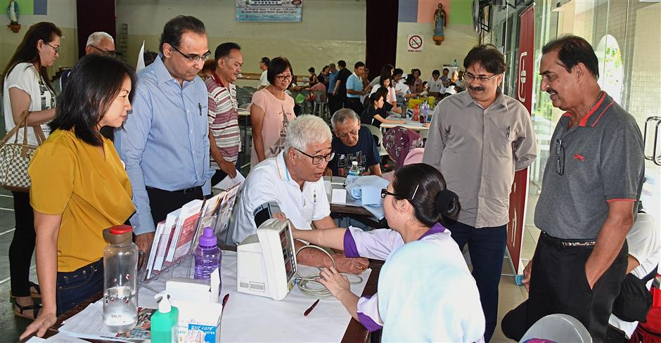(Left) Dr Teoh examining the eye of an elderly patient. (Below) Phee having his blood pressure checked during the Penang Health Carnival at the St Anne's Hall in Jalan Kulim, Bukit Mertajam. Looking on are (from left) Heng, Dr Ajay, Dr Paramjit and Dr Kulwaran. — Photos: M. SIVANANTHA SHARMA/The Star