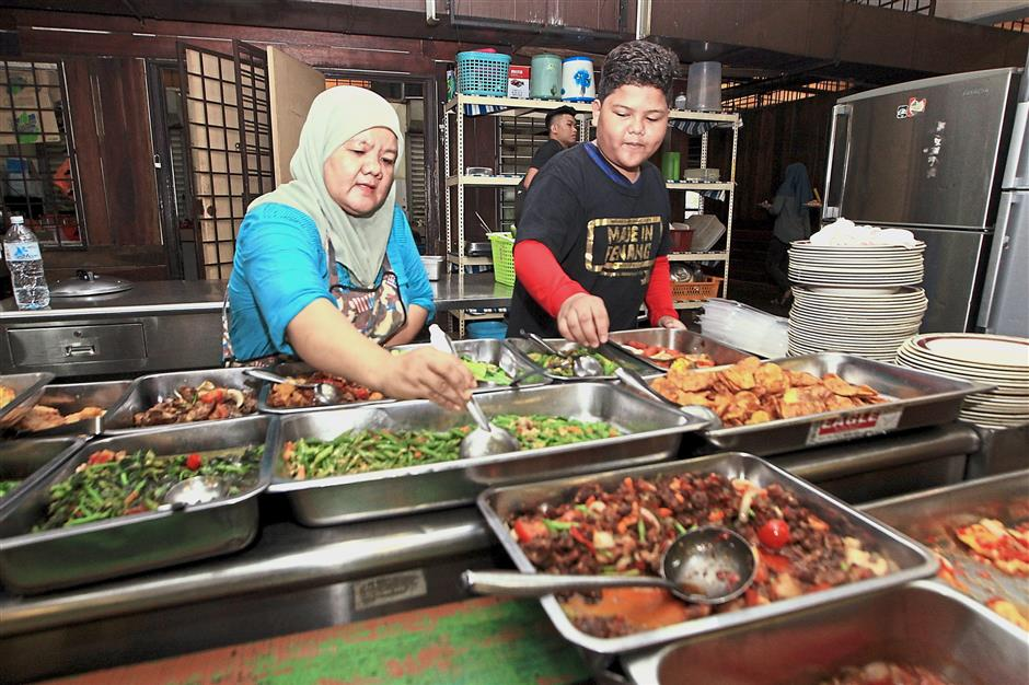 Siti Rohayu gets a little help from her son Mohd Aksyaffuddin Mohd Ayub (right) as the crowd builds up at lunch hour.