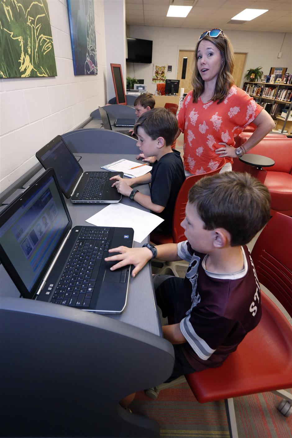 ADVANCE FOR RELEASE JUNE 10, 2019 AND THEREAFTER -  In this May 8, 2019, photograph, Sharon Stidham, standing, talks to her sons Graham, center, and Miles, front, as they use the laptops at East Webster High School to do homework in Maben, Miss. A cellphone tower is visible through the trees from their home on a hilltop near Maben, but the internet signal does not reach their house, despite building a special antenna on top of a nearby family cabin. (AP Photo/Rogelio V. Solis)
