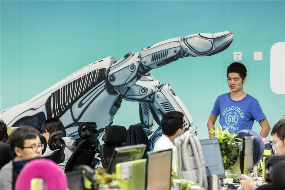 Employees work in front of a mural displaying a robotic hand inside Iflytek Co.\'s regional headquarters in Guangzhou, China, on Tuesday, Oct. 31, 2017. Iflytek, which specializes in voice recognition, is collaborating withu00a0Guangzhou Pharmaceutical Holdings Ltd. on a network of health centers that will rely partly on artificial intelligence for diagnosis and treatment. Photographer: Qilai Shen/Bloomberg