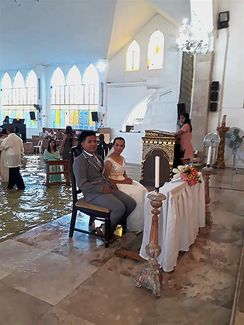 For wetter or worse: Delos Angeles and her groom during their wedding at a flooded church in Hagonoy town, north of Manila. — AFP
