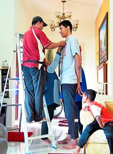 Tall order: The tailor taking Mohd Azli's measurements for his baju Melayu.