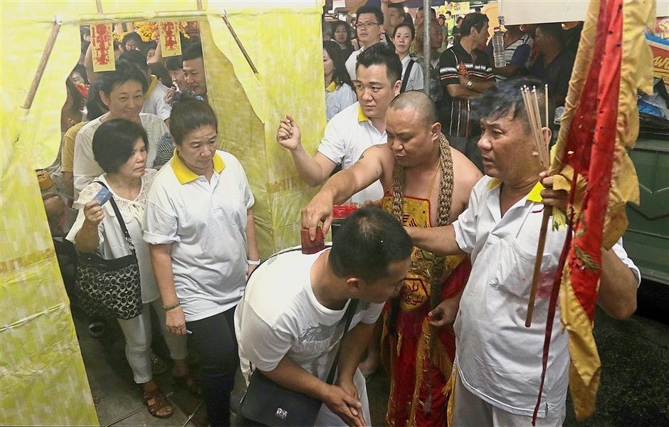 Devotees taking turns to pass through a yellow arch before getting the back of their shirts stamped with the sign of an amulet believed to give them protection from harm.