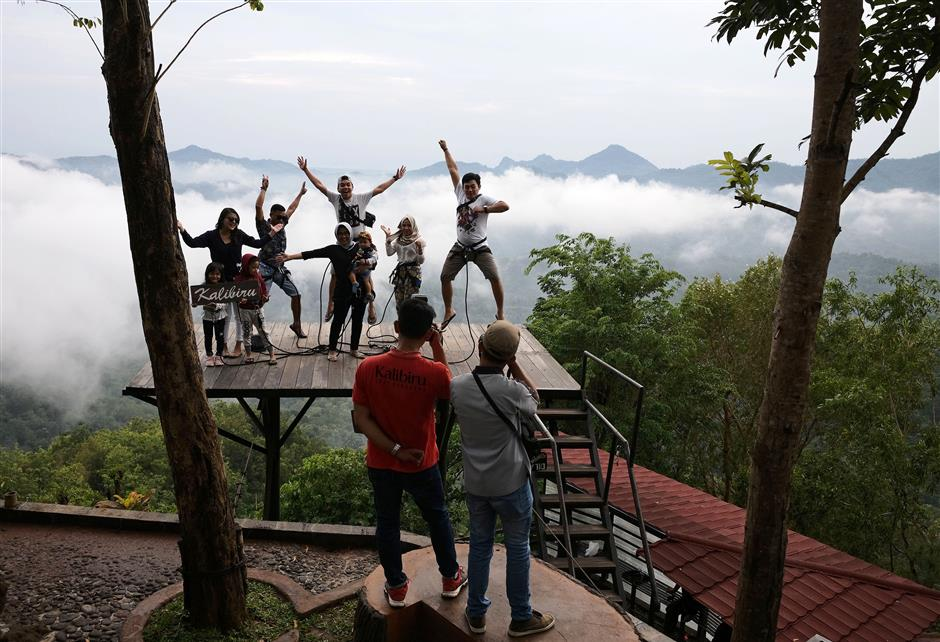 Visitors pose for photographs on a platform at the Kalibiru Tourism Village in Kulon Progo Regency, Special Region of Yogyakarta, Indonesia, on Saturday, Feb. 3, 2018. In Kalibiru, near Yogyakarta, villagers built treetop platforms to provide a full-fledged destination for social media photo-ops. They installed cameras and hired photographers to advise on the best poses to showcase the background of verdant hills and a shimmering blue reservoir. Photographer: Dimas Ardian/Bloomberg