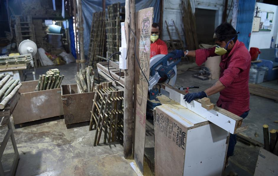 In this photo taken on September 19, 2018 workers cut bamboo as per measurements to manufacture a funeral cot, part of the SarvaPooja 'final rites kit,' at their factory in Mumbai. - When Parag Mehta had to arrange a second family funeral in two weeks he was distraught and short of time to get the 38 items for an elaborate Hindu ceremony -- so he went online and found a 'final rites kit'. (Photo by INDRANIL MUKHERJEE / AFP) / TO GO WITH: India-economy-internet-Amazon-death, FOCUS by Vishal MANVE