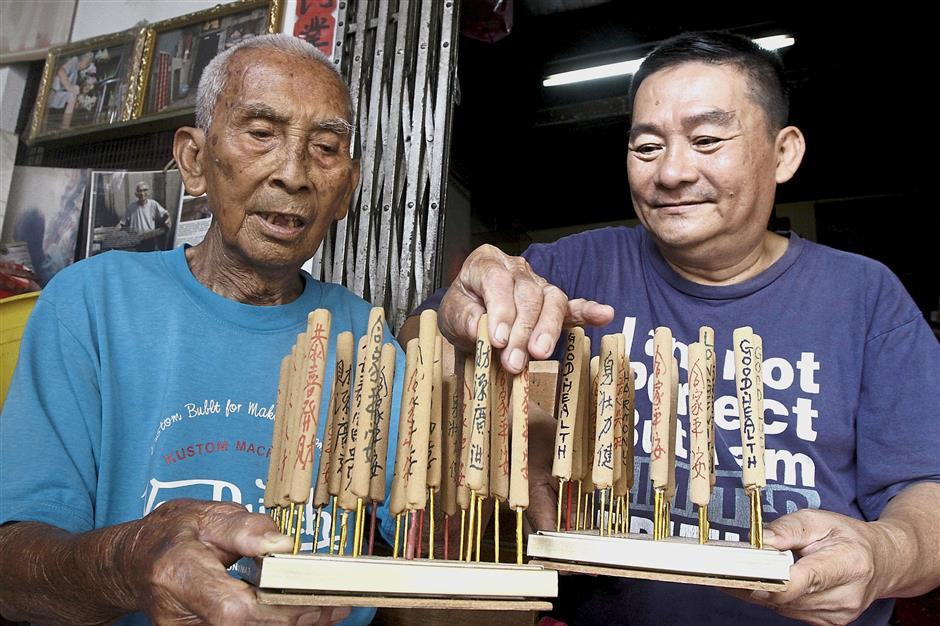 (From left) Beng Chuan and his son Chin Poh showing some of their handmade joss sticks at their rented shophouse in Lorong Muda, off Stewart Lane, in George Town.