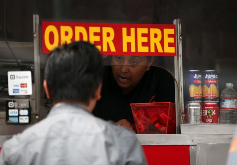 A customer places an order with a food truck in San Francisco, California. US core sales increased 0.6% last month, pointing to an economy that is firming up - AFP Photo.