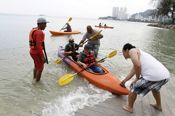 The Special Scouts were paired up with regular scouts while canoeing at Penang Water Sport Recreation Centre.(Right) Participants and volunteers playing bubbles at the camp.