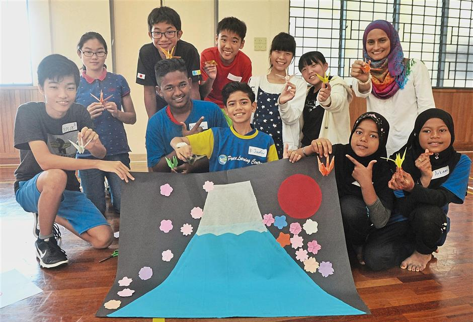 Penang Japanese School students and refugees showing off their artwork.