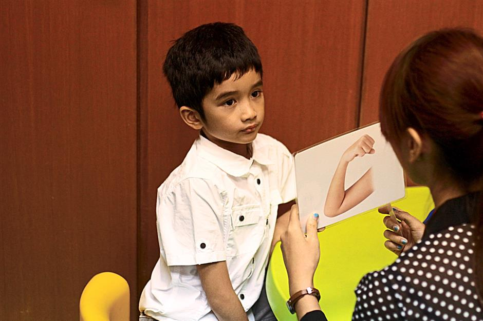 What is it? Afiq Adam, 7, identifying body parts from the flash card that his teacher Melissa Zu Reenais holding.