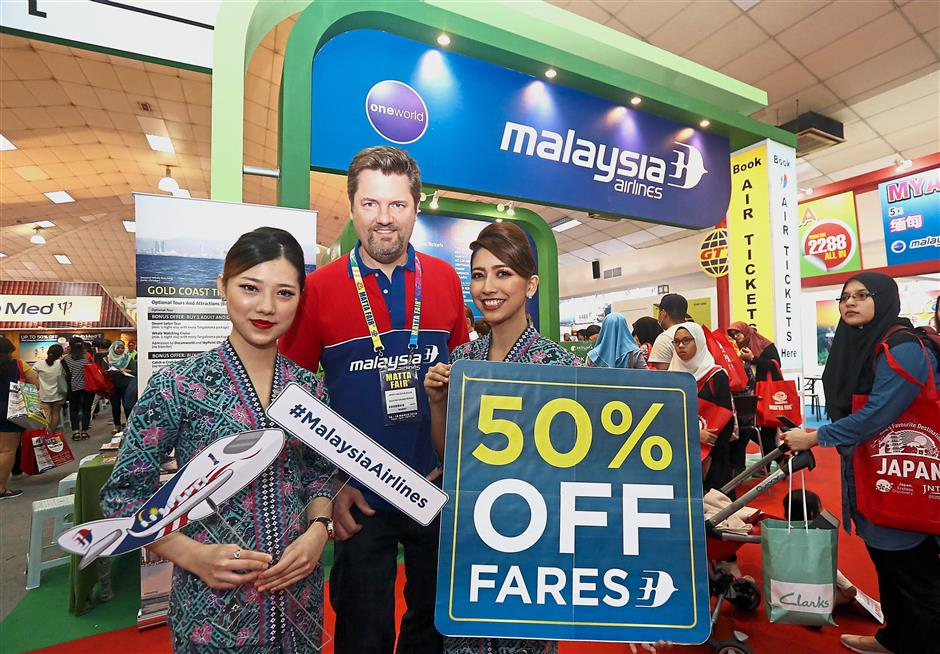 Muehlen (centre) at the Malaysia Airlines booth where discounts up to 50 on selected routes were offered to travellers.