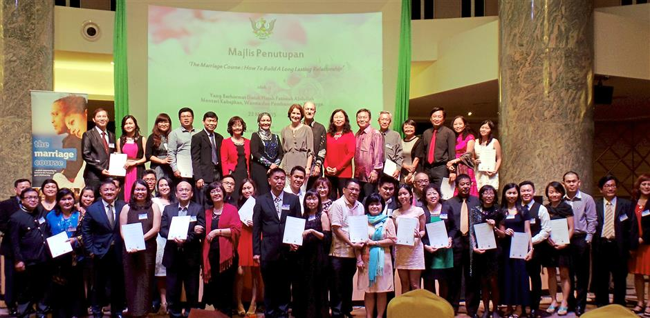 All 26 participants holding up their certificate of attendance for the marriage course.