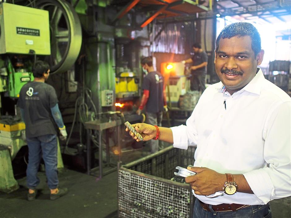 Proud: N.Sunderaj showing how a piece of metal is being perfected as an effective coupler as part of the scaffolding system atone of the contract manufacturers plants in Klang.