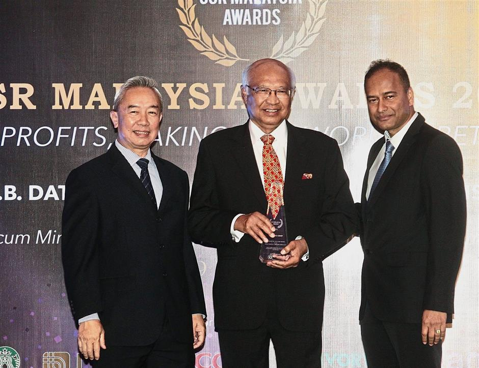 Good deeds recognised: Dr Mohd Aminuddin (centre) receiving the award from Rajendran and CSR Malaysia co-chairman Lee Seng Chee at the awards in Kuala Lumpur.