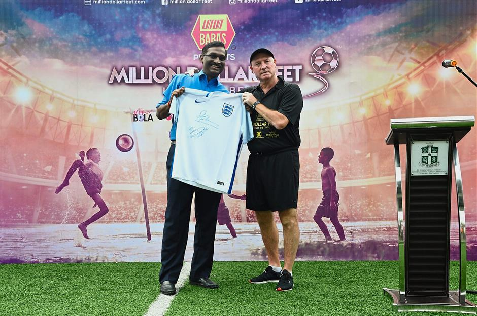Kamalanathan (left) receiving an exclusive signed England jersey from McMahon.