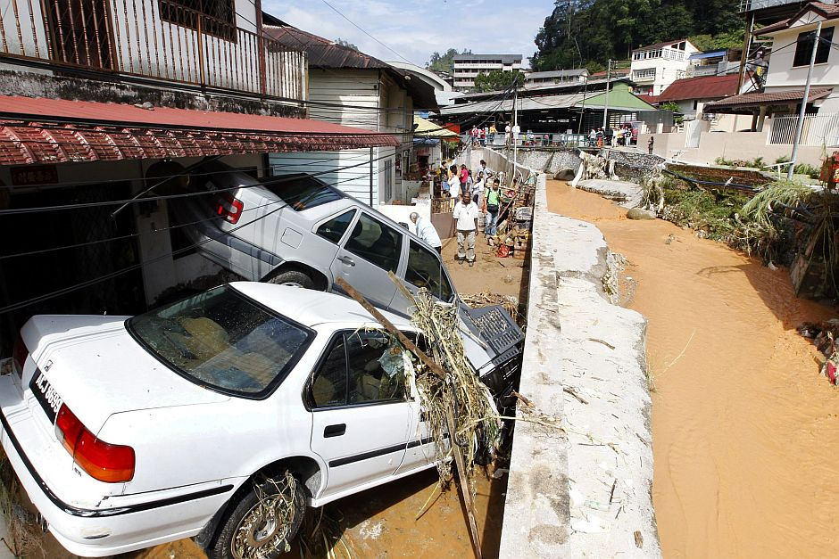 Scene of destruction: Cars smashed against a wall after being carried by the mudslide in Ringlet. — KAMARUL ARIFFIN / The Star