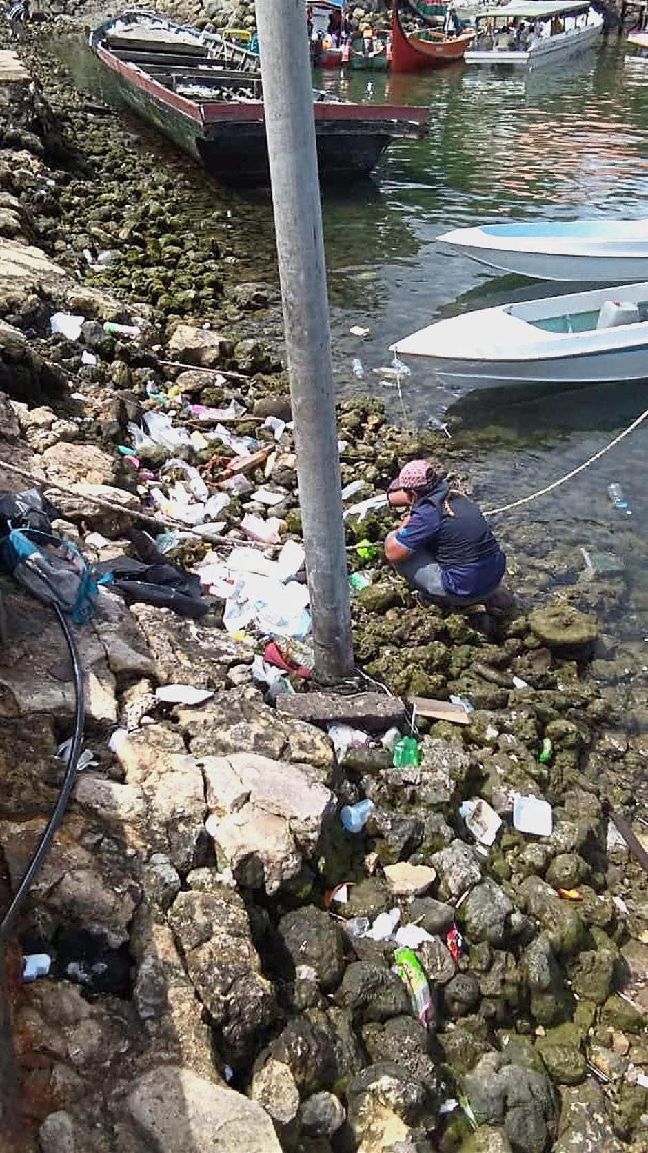 Cleaning the filth: A cleaner picking litter of plastics and other rubbish in Semporna during a campaign to clean the town over the past week.