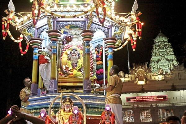 Devotees placing the statue of Lord Muruga onto the chariot.