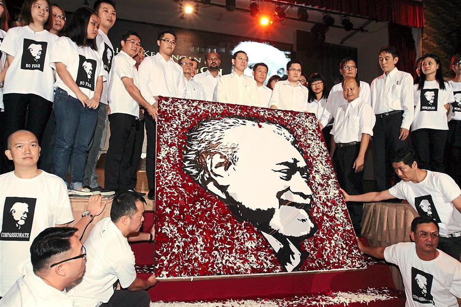 Senior DAP leaders together with the late Karpal Singh's fans posing with an artwork featuring his portrait during a memorial dedicated to the lawyer and outspoken leader.